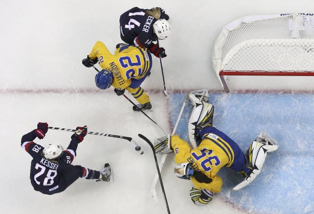 Team USA's Kessel shoots past Sweden's goalie Wallner to score during the first period of their women's semi-final ice hockey game at the Sochi 2014 Winter Olympic Games