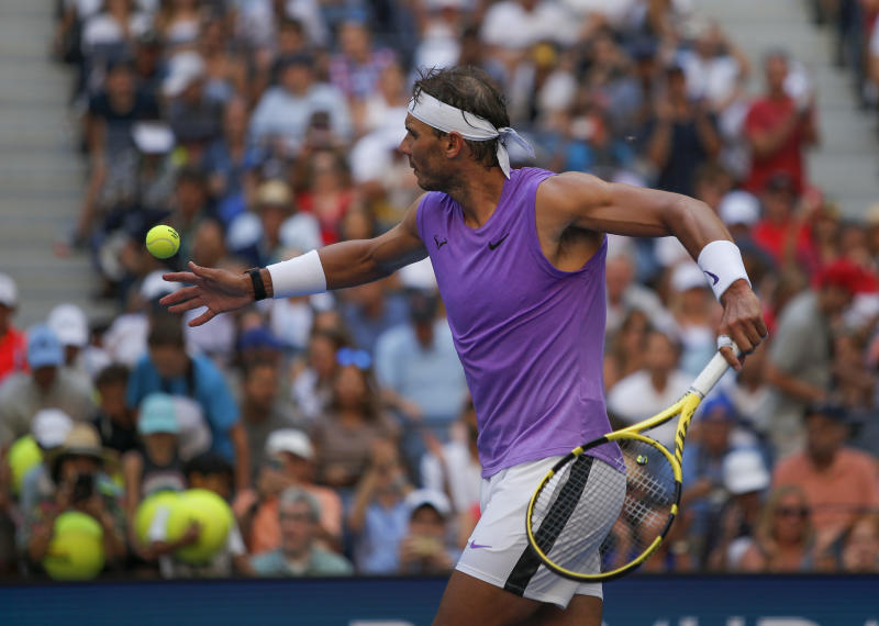 Rafael Nadal, of Spain, hits autographed balls into the grandstand after defeating Hyeon Chung, of South Korea, during round three of the US Open tennis championships Saturday, Aug. 31, 2019, in New York. (AP Photo/Eduardo Munoz Alvarez)