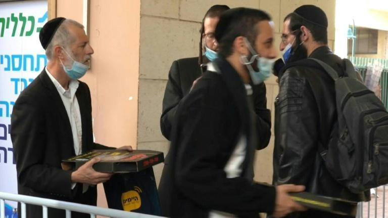 Israeli authorities distribute pizzas at a vaccination centre in the mainly ultra-Orthodox city of Bnei Brak