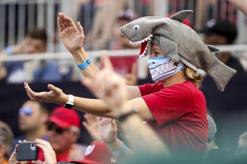 """In this Sept. 29, 2019, file photo, a fan wears a shark hat as Washington Nationals' Gerardo Parra comes up to bat in the eighth inning of a baseball game against the Cleveland Indians at Nationals Park in Washington. Creators of the viral video """"Baby Shark,"""" whose """"doo doo doo"""" song was played at the World Series in October, are developing a version in Navajo. (AP Photo/Andrew Harnik, File)"""