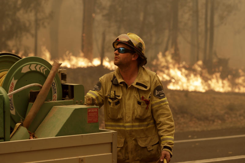 A Forest Corporation worker manages a fire hose as he battles a fire near Moruya, Australia, Saturday, Jan. 4, 2020. Australia's Prime Minister Scott Morrison called up about 3,000 reservists as the threat of wildfires escalated Saturday in at least three states with two more deaths, and strong winds and high temperatures were forecast to bring flames to populated areas including the suburbs of Sydney. (AP Photo/Rick Rycroft)