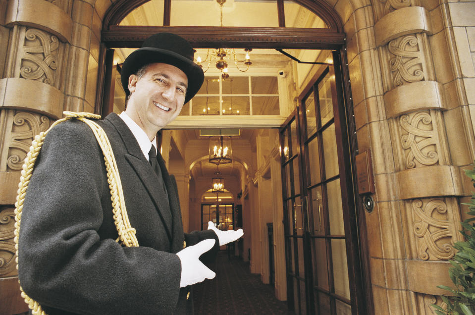 Doorman Gesturing Towards a Hotel Entrance