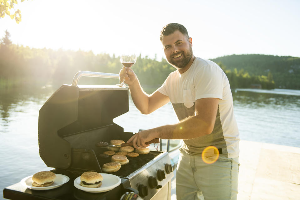 A father family preparing hamburger on a grill outdoors close to a lake