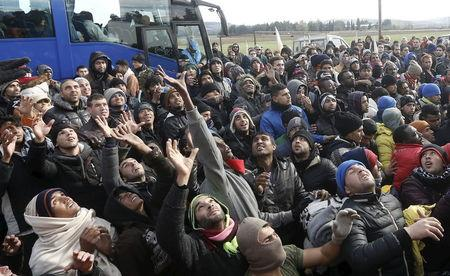Stranded migrants raise their hands to grab goods given away by locals at the Greek-Macedonian borders near the Greek village of Idomeni