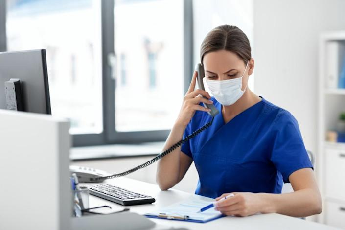 female doctor or nurse wearing face protective medical mask for protection from virus disease with computer and clipboard calling on phone at hospital