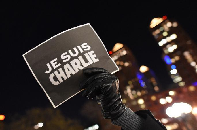 "A man holds a sign reading ""I Am Charlie"" as people gather on Union Square January 7, 2015 in New York"