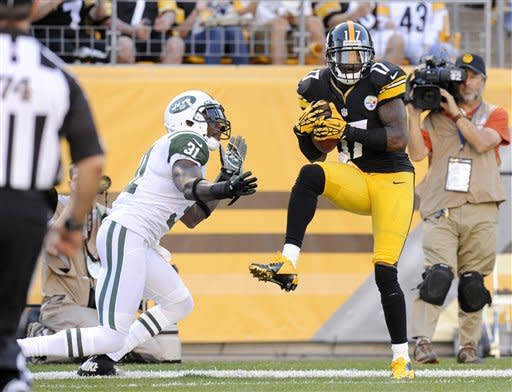 Pittsburgh Steelers wide receiver Mike Wallace (17) makes a catch for a touchdown in front of New York Jets cornerback Antonio Cromartie (31) in the third quarter of an NFL football game on Sunday, Sept. 16, 2012, in Pittsburgh. The touchdown call was confirmed after replay. (AP Photo/Don Wright)