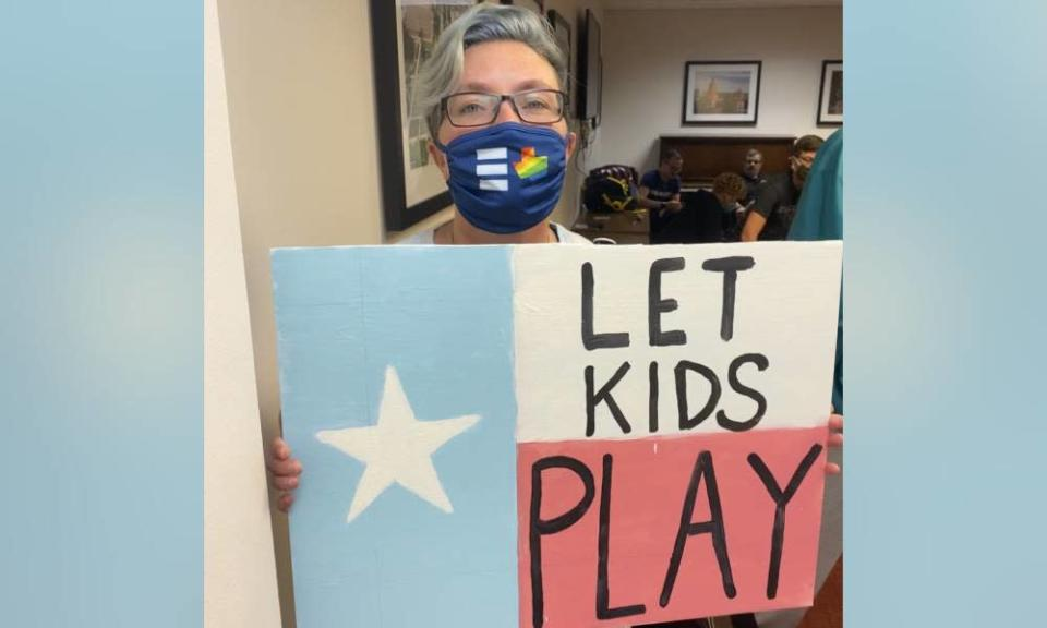 Picture of Hillary Moore-Embry who is a parent fighting anti-trans legislation in Texas, they hold up a sign that reads 'let kids play'