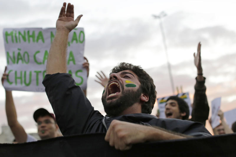 A demonstrator shouts during a protests in Sao Paulo, Brazil, Monday, June 17, 2013. Protesters massed in at least seven Brazilian cities Monday for another round of demonstrations voicing disgruntlement about life in the country, raising questions about security during big events like the current Confederations Cup and a papal visit next month. (AP Photo/Nelson Antoine)