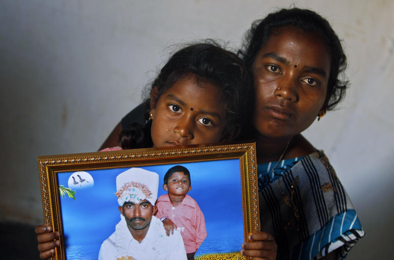 In this photo taken Feb. 14, 2012, Shwetha, 5, sits on the lap of her mother Sunita, 22, as she holds a photograph of her debt-ridden father Hari Prasad, who consumed fertilizer chemical to kill himself on Aug. 1, 2010, in Kadiri village about 160 kilometers (99 miles) north of Bangalore, India. A wave of suicides among the impoverished residents of India's Andhra Pradesh state was blamed on the relentless tactics of agents from microfinance companies, which give small loans intended to lift up the very poor. (AP Photo/Aijaz Rahi)