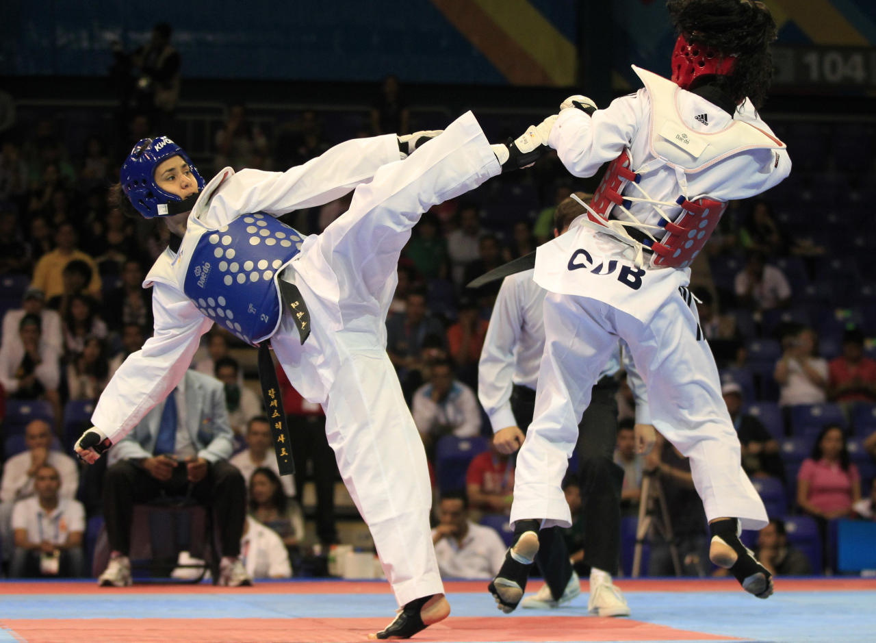 Mexico's Irma Contreras, left, and Cuba's Irma Munoz, fight during a semifinal women's taekwondo -57 kg match at the Pan American Games in Guadalajara, Mexico, Sunday, Oct. 16, 2011. (AP Photo/Martin Mejia)