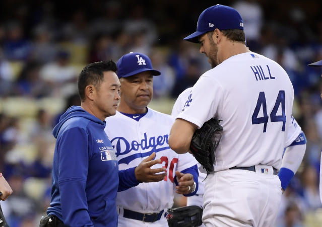Los Angeles Dodgers starting pitcher Rich Hill, right, is taken out of the game by manager Dave Roberts, center, due to an injury prior to the second inning of the team's baseball game against the San Francisco Giants on Wednesday, June 19, 2019, in Los Angeles. (AP Photo/Mark J. Terrill)