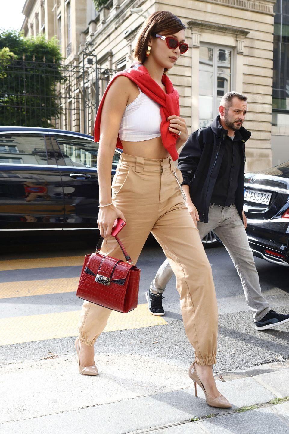 <p>In a red sweater, white crop top, high-waisted khaki trousers, red crocodile handbag, Santoni pumps and Versace sunglasses while out in Paris.</p>