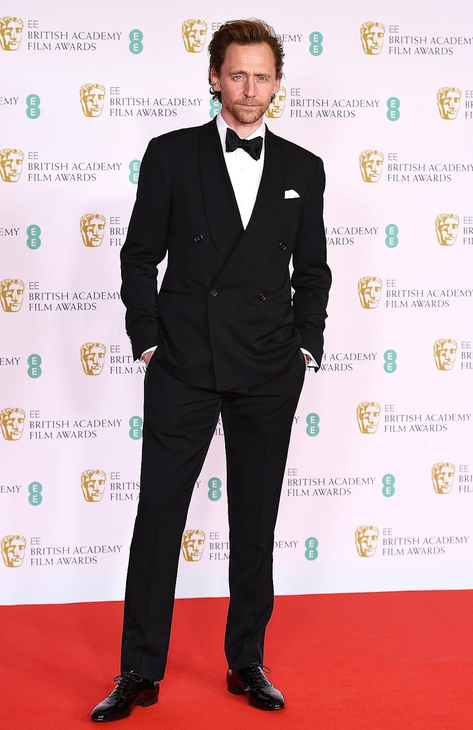 <p>in a black tuxedo and bow tie. </p>