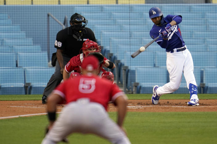 Los Angeles Dodgers' Mookie Betts connects on a solo home run during the first inning of a spring training exhibition baseball game against the Los Angeles Angels Tuesday, March 30, 2021, in Los Angeles. (AP Photo/Marcio Jose Sanchez)