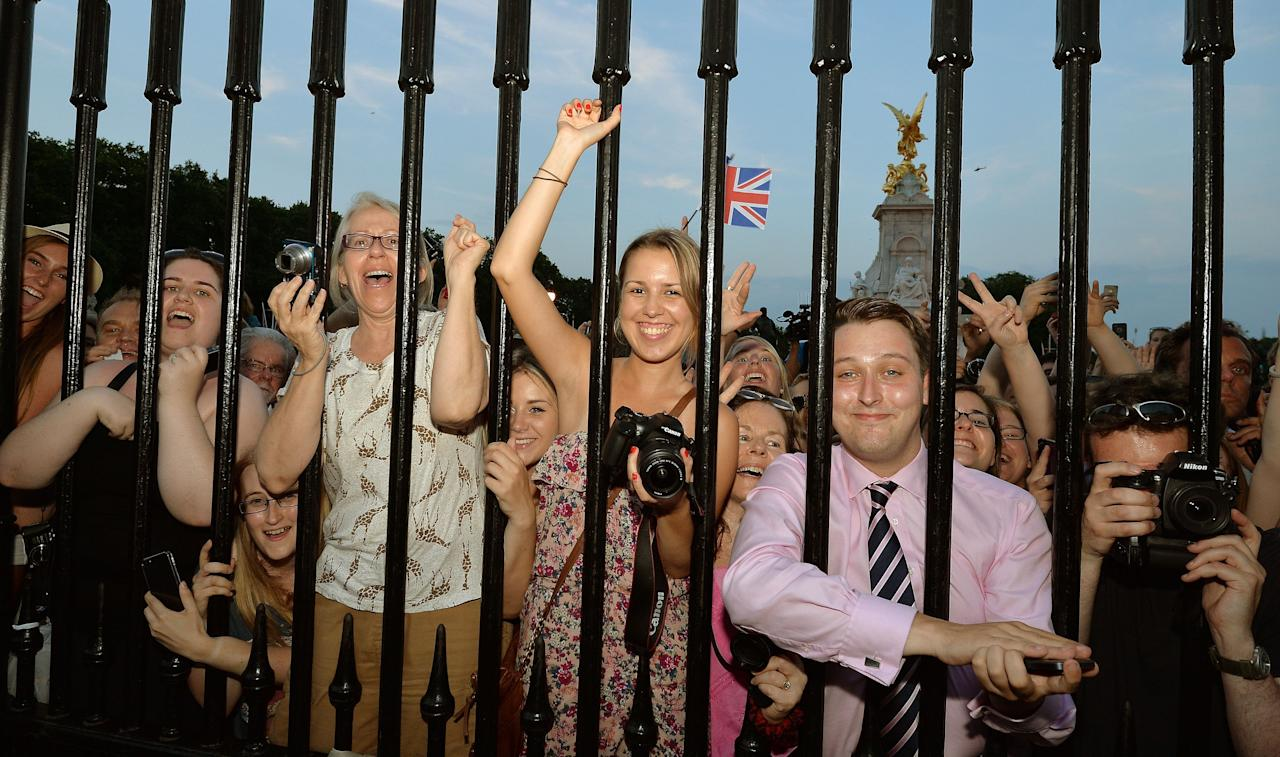 The large waiting crowds cheers as the Queen's Press Secretary Ailsa Anderson with Badar Azim a footman place on an easel in the Forecourt of Buckingham Palace a notification, to announce the birth of a baby boy, at 4.24pm to the Duke and Duchess of Cambridge at St Mary's Hospital in west London.