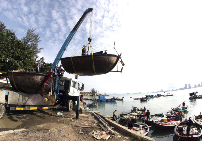 People move fishing boats to save place ahead of Typhoon Molave in Danang, Vietnam on Monday, Oct. 26, 2020. National agency forecasts the typhoon to hit Vietnam on Wednesday morning in the central region where 1.3 people could face evacuation. (Tran Le Lam/VNA via AP)
