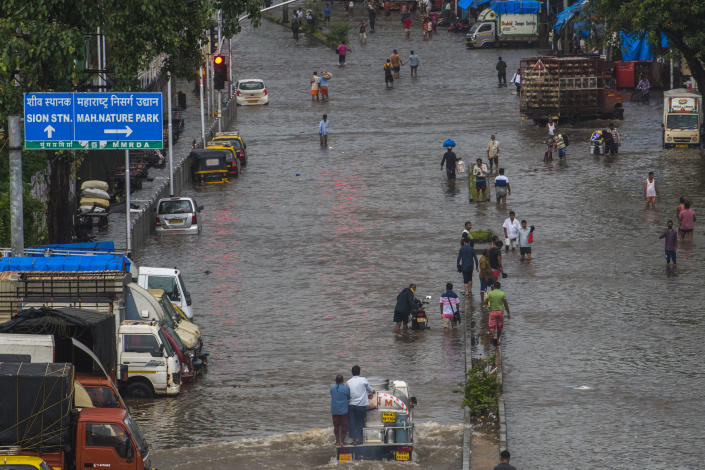MUMBAI, INDIA - JULY 18: Commuters wade through a waterlogged road after heavy rain, at Sion, on July 18, 2021 in Mumbai, India. (Photo by Pratik Chorge/Hindustan Times via Getty Images)