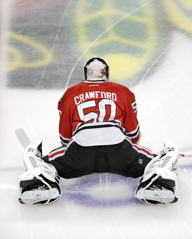 Chicago Blackhawks goalie Corey Crawford stretches before Game 1 of the Western Conference finals in the NHL hockey Stanley Cup playoffs against the Los Angeles Kings in Chicago on Sunday, May 18, 2014. (AP Photo/Charles Rex Arbogast)
