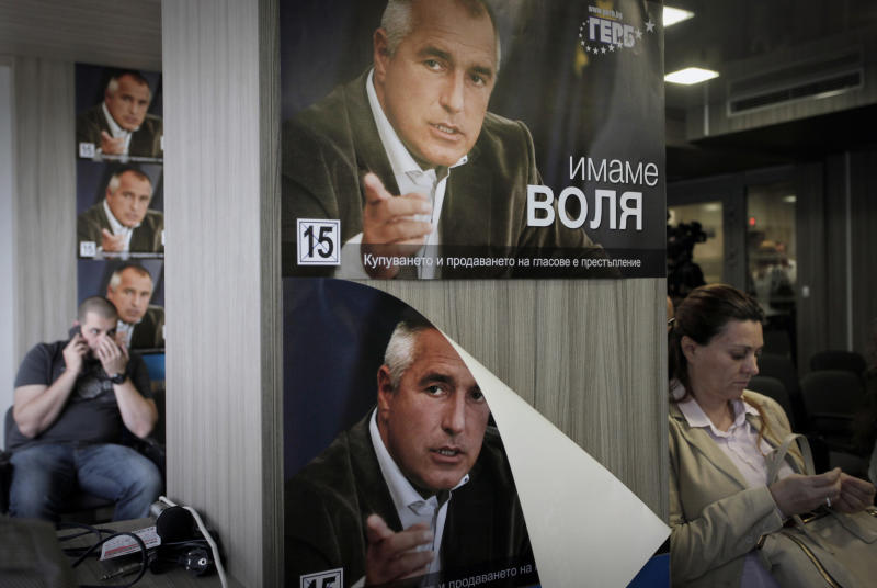 Journalists wait in  a press-room covered with posters of Boyko Borisov, former Prime Minister and leader of center-right GERB party,  in Sofia, Tuesday, May 14, 2013. The center-right party of former Prime Minister Boiko Borisov has fallen far short of winning a majority needed to form a government, according to nearly final election results released on Monday, and appears to have no willing partners to join a coalition. (AP Photo/Valentina Petrova)