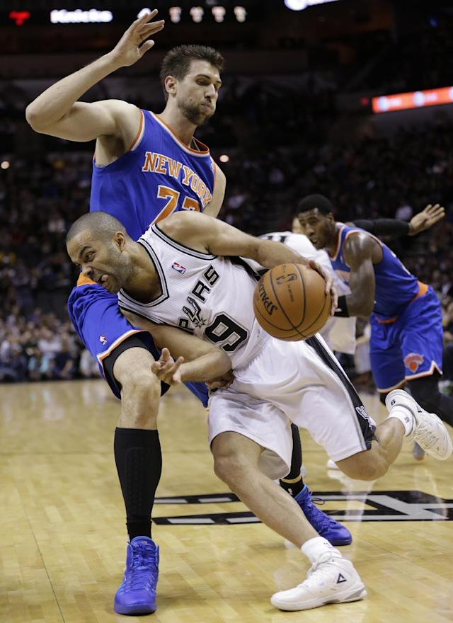 San Antonio Spurs' Tony Parker (9) drives around New York Knicks' Andrea Bargnani during the first half on an NBA basketball game, Thursday, Jan. 2, 2014, in San Antonio. (AP Photo/Eric Gay)