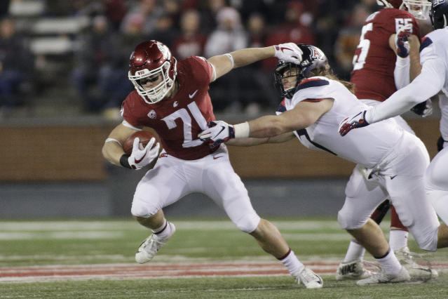 """FILE - In this Nov. 17, 2018, file photo, Washington State running back Max Borghi (21) runs while under pressure from Arizona linebacker Colin Schooler during the first half of an NCAA college football game in Pullman, Wash. The departure of James """"Boobie"""" Williams should mean more exposure for Borghi, who earned a starting job last year as a freshman and is expected to be the primary option in the backfield. (AP Photo/Young Kwak, File)"""