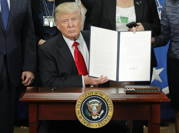 President Donald Trump with one of the executive orders he signed on Wednesday. (Photo: Pablo Martinez Monsivais/AP)