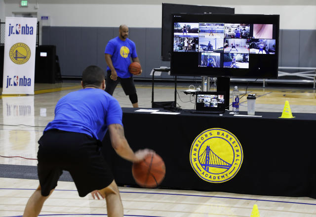 In this photo taken on Tuesday, June 9, 2020, coach Jose Rivera goes through a drill with his virtual students at Golden State Warriors basketball camp in Oakland, Calif. The Warriors had to adapt their popular youth basketball camps and make them virtual given the COVID-19 pandemic. (AP Photo/Ben Margot)