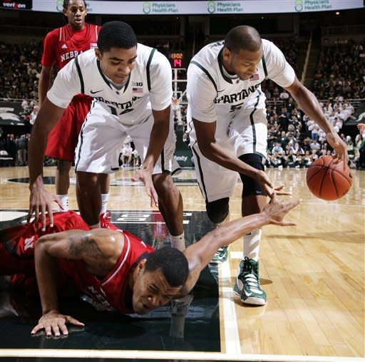 Nebraska's Dylan Talley, bottom, and Michigan State's Gary Harris, left, and Adreian Payne, right, fight for a loose ball during the first half of an NCAA college basketball game, Sunday, Jan. 13, 2013, in East Lansing, Mich. Michigan State won 66-56. (AP Photo/Al Goldis)
