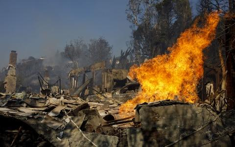 Flames burn from a destroyed home's natural gas line during the Skirball Fire in the Bel Air neighborhood of Los Angeles - Credit: Bloomberg