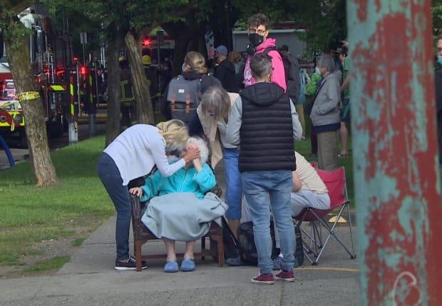 Family and neighbours comfort an elderly woman following a fire in her apartment in Vancouver's West End on Thursday. (Maggie MacPherson/CBC - image credit)