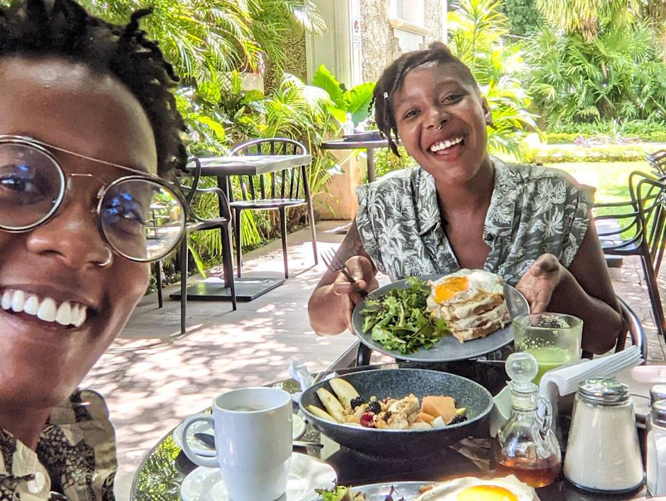 Amber and her partner posing with their food at an outdoor table