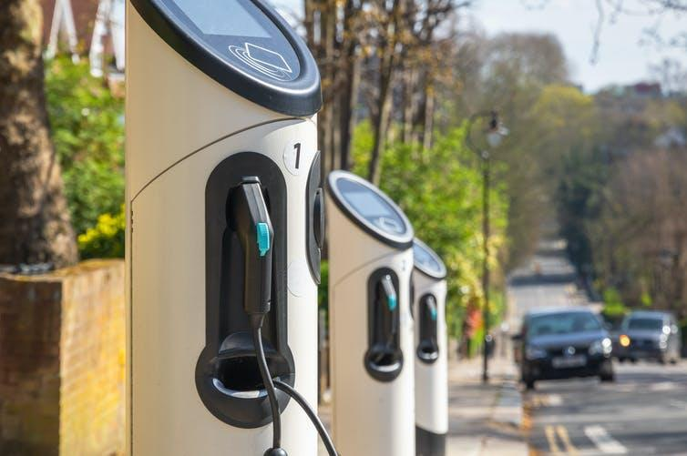 A row of three electric vehicle charging points beside a road in London.