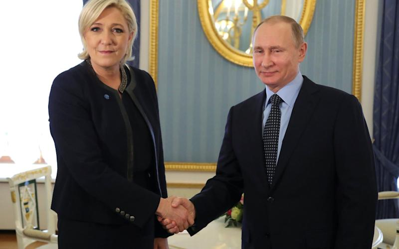 Russian President Putin shakes hands with French far-right party leader Le Pen during their meeting in Moscow - REUTERS