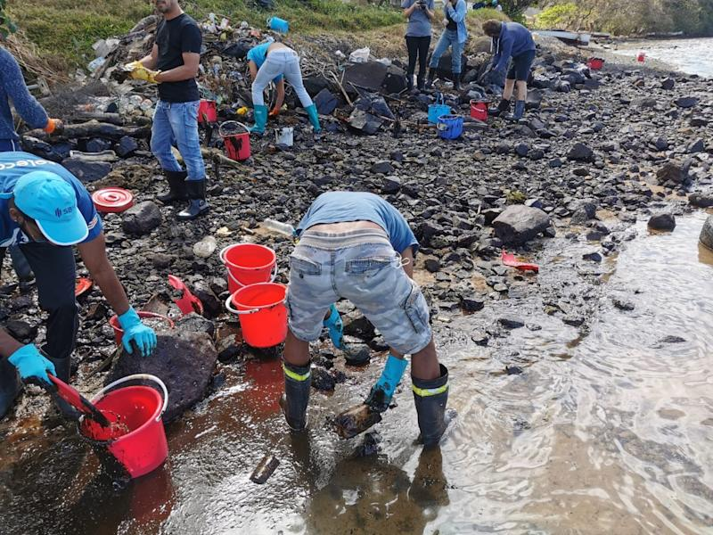 On the beach, locals clean up the oil using red buckets.