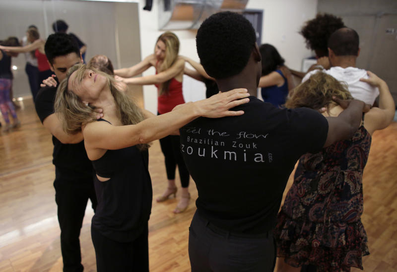 In this Monday, April 21, 2014 photo, Carmen Marshall, 42, of Miami, second from left, closes her eyes while dancers massage each other during a Brazilian zouk dance class at the VK Dance Studio in North Miami Beach, Fla. Zouk dance and music, born in the French Caribbean, adopted in Brazil and spread through Latin America and Europe, is now taking root in the United States.(AP Photo/Lynne Sladky)