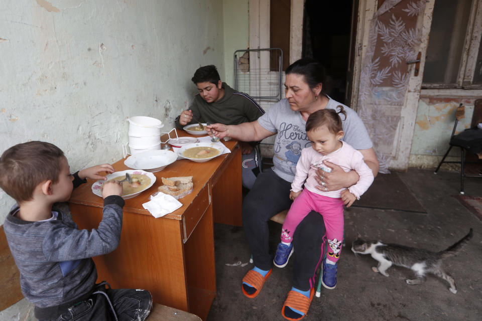 Members of the Hungarian Roma Bastyur family eat lunch outside their home in Bodvaszilas, Hungary, Monday, April 12,2021. Many students from Hungary's Roma minority do not have access to computers or the internet and are struggling to keep up with online education during the pandemic. Surveys show that less than half of Roma families in Hungary have cable and mobile internet and 13% have no internet at all. (AP Photo/Laszlo Balogh)
