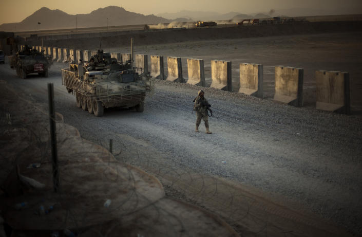 """FILE - In this Aug. 8, 2009, file photo, U.S. soldiers from the 5th Striker Brigades walk next to armored vehicles as they arrive at their base on the outskirts of Spin Boldak, about 100 kilometers (63 miles) southeast of Kandahar, Afghanistan. President Joe Biden and his NATO counterparts bid a symbolic farewell to Afghanistan on Monday, June 14, in their last summit before America winds up its longest """"forever war"""" and the military pulls out for good. (AP Photo/Emilio Morenatti, File)"""
