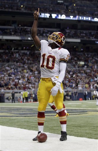 Washington Redskins quarterback Robert Griffin III celebrates after scoring on a 5-yard run during the first quarter of an NFL football game against the St. Louis Rams, Sunday, Sept. 16, 2012, in St. Louis. (AP Photo/Seth Perlman)