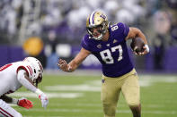 Washington's Cade Otton (87) tries to avoid a tackle as he runs with the ball against Arkansas State in the first half of an NCAA college football game, Saturday, Sept. 18, 2021, in Seattle. (AP Photo/Elaine Thompson)