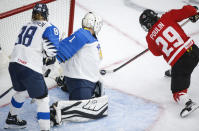 Finland goalie Anni Keisala, center, blocks a shot from Canada's Marie-Philip Poulin, right, as Finland's Ronja Savolaine looks on during the second period of an IIHF women's hockey championship game in Calgary, Alberta, Friday, Aug. 20, 2021. (Jeff McIntosh/The Canadian Press via AP)