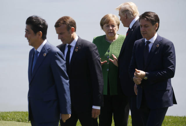 <p>Japan's Prime Minister Shinzo Abe, France's President Emmanuel Macron and Italy's Prime Minister Giuseppe Conte walk away as Germany's Chancellor Angela Merkel talks with President Donald Trump after a family photo at the G7 Summit in the Charlevoix city of La Malbaie, Quebec, Canada, June 8, 2018. (Photo: Leah Millis/Reuters) </p>