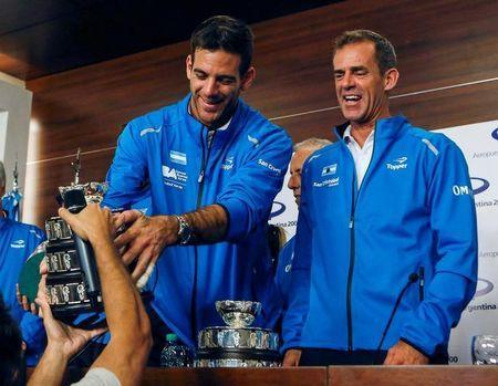 Juan Martin del Potro of Argentina's Davis Cup tennis team, holds a trophy next to captain Daniel Orsanic upon their arrival in Buenos Aires, Argentina, November 29, 2016. REUTERS/Agustin Marcarian