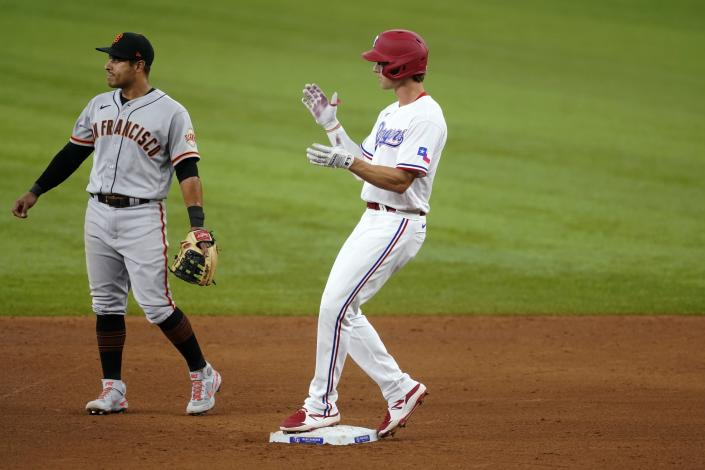 San Francisco Giants second baseman Donovan Solano, left, stands by the bag as Texas Rangers' Eli White celebrates his double in the sixth inning of a baseball game in Arlington, Texas, Wednesday, June 9, 2021. (AP Photo/Tony Gutierrez)