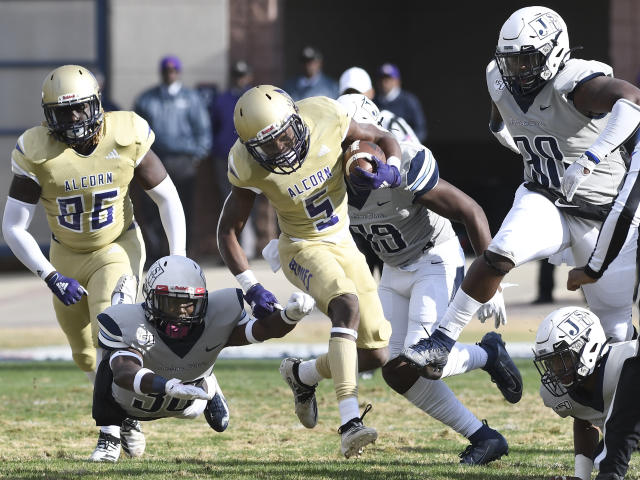 Alcorn State running back Niko Duffey (5) carries the ball on a run while avoiding Jackson State defenders during the first half of an NCAA college football game in Jackson, Miss., Saturday, Nov. 23, 2019. (Courtland Wells/The Vicksburg Post via AP)