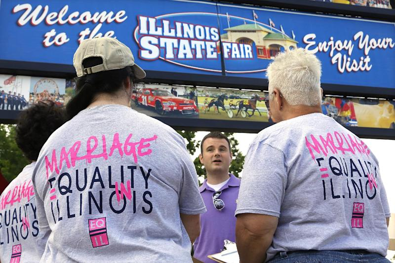 In this Wednesday, Aug. 14, 2013 photo, Randy Hannig, center, of Equality Illinois, hands out shirts supporting gay marriage and explains how people can help support the cause during the Illinois State Fair in Springfield, Ill. After their campaign to legalize gay marriage fizzled in Illinois this year, advocates set aside their disappointment and gave their campaign a serious makeover. (AP Photo/Seth Perlman)
