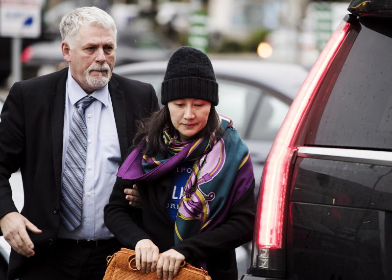 Huawei chief financial officer Meng Wanzhou arrives at a parole office with a security guard in Vancouver, British Columbia, Wednesday, Dec. 12, 2018. (Darryl Dyck/The Canadian Press via AP)