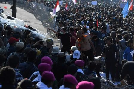 Protesters gesture to riot police officers during a protest in Surabaya