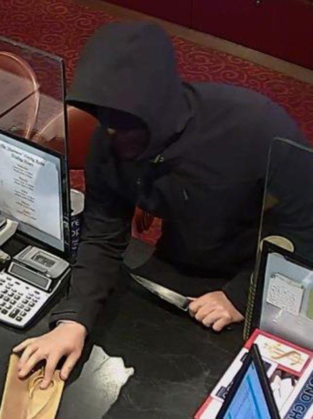 A robber holds up a terrified pokies cashier with a knife and demands cash before fleeing. Picture: Victoria Police