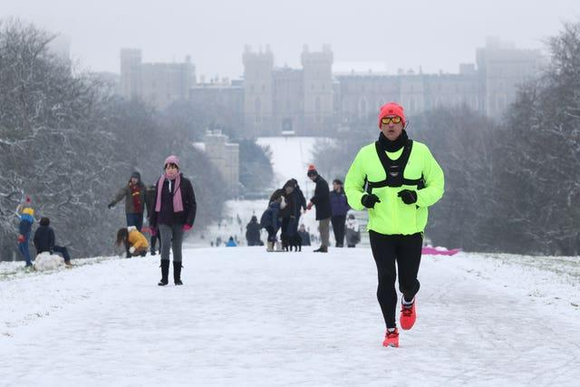 A jogger in the snow on the Long Walk at Windsor Castle, Berkshire